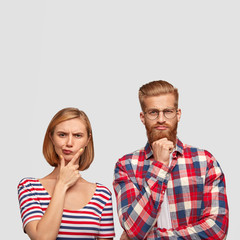 Thoughtful young groupmates try to find solution, have pensive clever expressions, hold chins, look seriously into camera. Attractive red haired guy with ginger beard collaborates with pretty female
