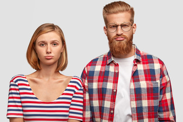Displeased husband and wife can`t find good apartment with modern conviniences to rent for suitable price, have sullen expressions. Gloomy hipster guy with thick red beard and his lovely girlfriend