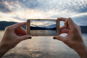 Taking a picture with a cellphone of the beautiful sunset. Taken in Whytecliff Park, Horseshoe Bay, West Vancouver, BC, Canada.