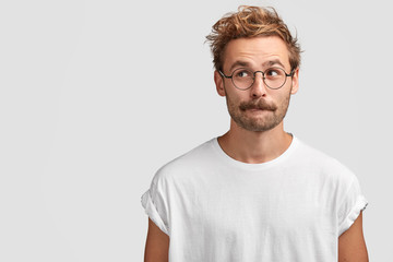 Puzzled handsome male with mustache, bites lower lip and looks curiously aside, thinks about something, dressed in casual white t shirt, stands against blank wall with copy space for your text Wall mural