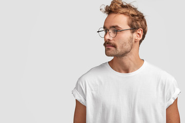 Profile shot of serious stylish hipster looks aside with confident expression, turns head aside, looks at something into distance, wears round spectacles, isolated over white background, blank space