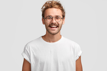 Horizontal shot of happy hipster male with toothy smile, wears casual white t shirt and glasses, being in good mood after unforgettable journey with girlfriend, isolated on white background.