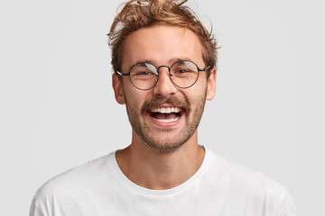 Close up shot of happy stylish male in round glasses, has positive smile on face, glad to recieve salary, going to spend money on new purchases, isolated over white background. People and lifestyle