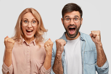Happy young colleagues or business partners rejoice success, clench fists and exclaim with triumph, have prosperous own company, high profits, stand next to each other against white background