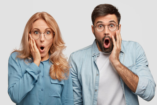 Scraed emotive family couple look with astonishment, being puzzled as notice robbers in their house, open mouthes widely, stand closely to each other. People, relationship and emotions concept