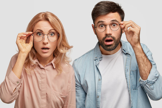 Stunned beautiful female and his male partner, looks with eyes full of disbelief, stare through glasses, recieve bad news about their business and falling sales, isolated on white studio wall