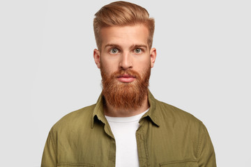 Studio shot of handsome hipster has ginger beard, trendy hairstyle, looks seriously directly at camera, contemplates about future job, dressed in stylish shirt, poses against white studio wall