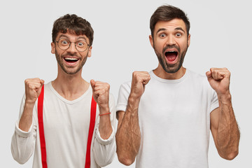 Wall Mural - Photo of joyful unshaven two young men clench fists and shout with happiness, dressed casually, isolated on white background, rejoice success and winning, feel optimism, have attractive looks