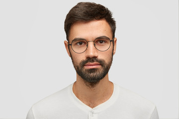 Close up portrait of handsome unshaven male with thick beard and mustache, has dark hair, looks seriously at camera, thinks about something, isolated over white background. Facial expressions concept