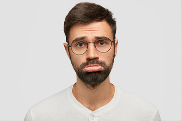 Sullen unshaven male with displeased expression, curves lower lip, has miserable expression, being abused as wife didn`t give him keys from auto, isolated over white background. Insult and people