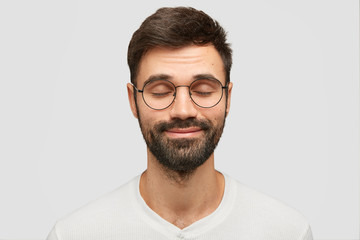 Pleased young Caucasian male closes eyes and imagines something pleasant, dreams about incredible things, wears spectacles, has dark bristle, isolated over white background. People and emotions