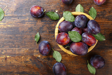 ripe plums in a wooden plate