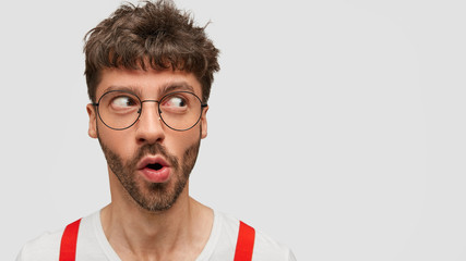 Photo of funny bearded male being wondered by what he sees, looks aside, expresses astonishment, looks mysteriously on white blank space, wears round glasses. Unshaven student wonk says: Omg