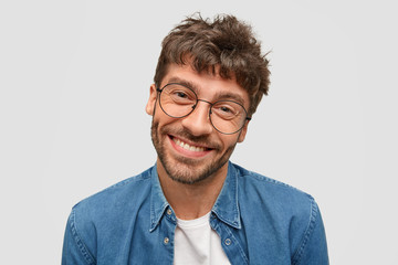 Isolated shot of positive bearded male with friendly smile, being in high spirit as spends free time with beautiful woman, pleased to recieve positive answer on propsal, stands against white wall