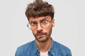 Close up shot of serious male boss with trendy hairdo looks in bewilderment at camera, frowns eyebrows, purses lips, has dark stubble, being annoyed with something. Negative facial expressions