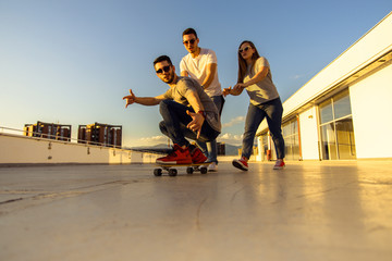YOUNG FRIENDS WITH SKATEBOARD AT THE TOP OF THE BUILDING AT SUNSET. Young and careless friends having fun concept.
