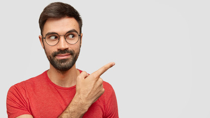 Horizontal shot of handsome bearded male with trendy hairdo, dressed in casual red t shirt, looks curiously asdie, points with index finger aside, shows free space for your advertising content