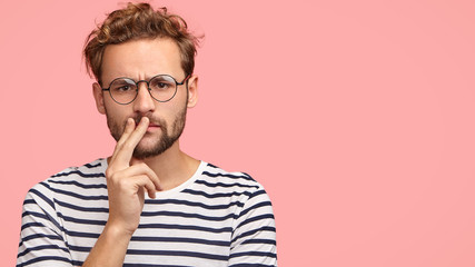 Horizontal shot of serious displeased man frowns face, keeps hand on mouth, has curly hair and stubble, wears striped t shirt, round spectacles, stands against pink background with copy space