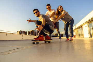 Portrait of adult friends while driving skateboard on the terrace. Young and careless friends having fun concept.