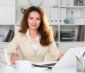 Portrait of businesswoman who is working with documents behind laptop