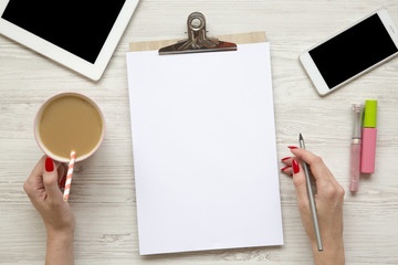 Feminine work space with tablet, noticepad, sheet, latte, smartphone and female hands over white wooden background, top view.