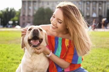 Cute yellow labrador retriever with owner outdoors