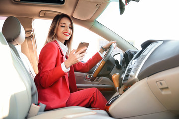 Young businesswoman with smartphone on driver's seat of car