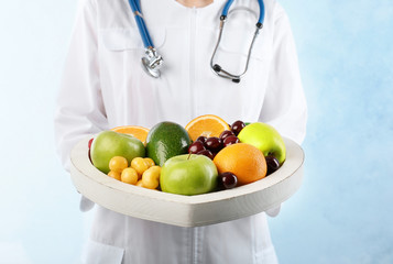 Female doctor holding plate with fresh fruits on light background. Cardiac diet