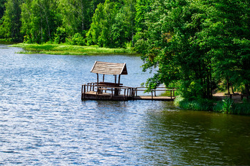Relaxing gazebo built on the river against the forest