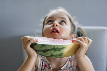 Little girl eating watermelon on the table