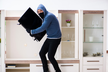 Man burglar stealing tv set from house