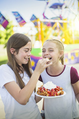 Two laughing and smiling teenage girls eating a funnel cake at an outdoor carnival or amusement park. Cute expression in this candid photo