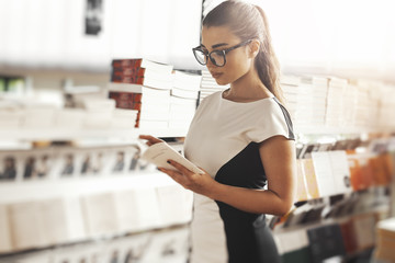 Young attractive woman reading book in a book store next to book shelf.