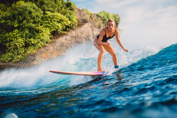 Surfer woman ride at surfboard on ocean wave. Woman in ocean during surfing.
