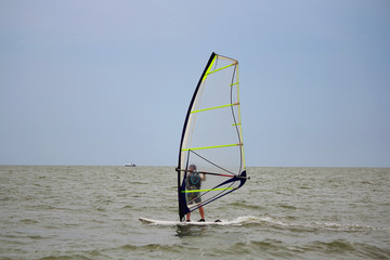 One windsurfer in the sea on a cloudy day. Selective focus, copy space.
