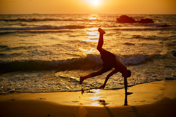 Young boy play capoeira at the beach. Child is happy and have fun to make sports near the sea during sunset. Best summer vacation upside down. Silhouette of boy making acrobatic tricks. Freedom.