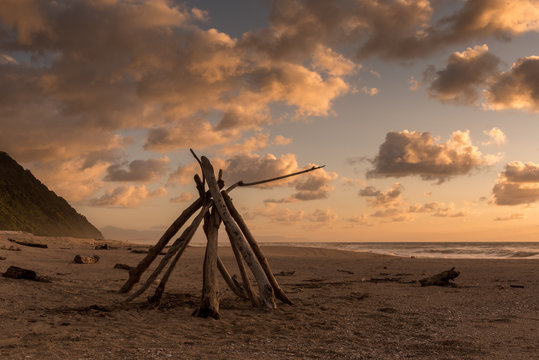 Pyramid of driftwood on the beach at sunset at the end of the Heaphy Track, Tasman, New Zealand.