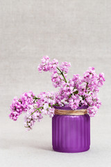 Vase with lilac flowers on cloth background with copy space. Pink flowers. Minimal concept.