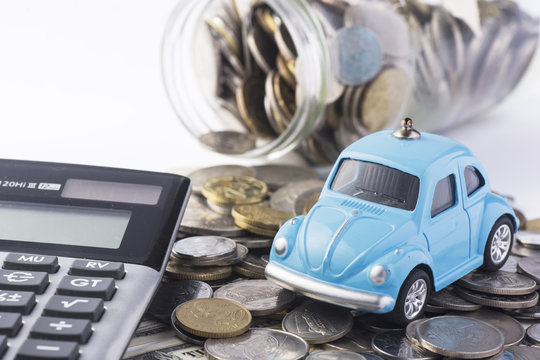 Close up blue car with calculator and coin.- Selective focus in car.- Image concept for car insurance and financial.