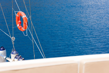 Background for a sea voyage on a yacht. Red lifebuoy, parapet boats and blue sea