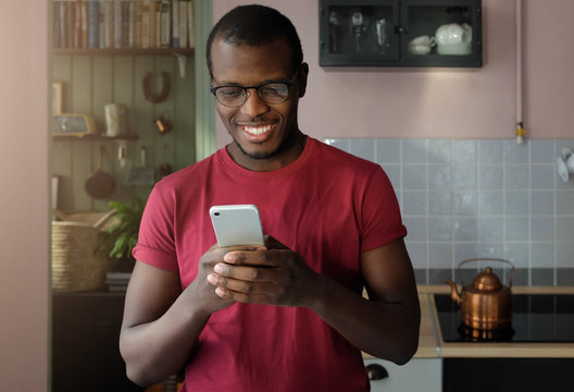 Closeup photo of African American man standing in cozy kitchen, looking at screen of cellphone, browsing web pages and smiling nicely while chatting