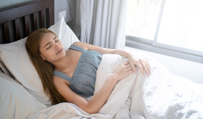 The girl sleeping on comfortable white bed, happy dream in the room, Instagram color, copy space on white background.