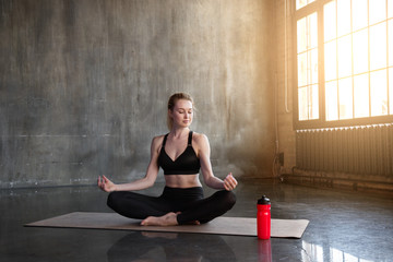 A beautiful, young, slender, strong woman in a loft-style gym with sun-drenched sunlight sits in a lotus pose and meditates.