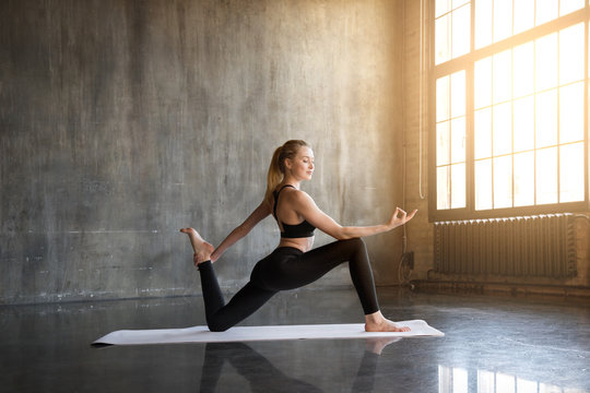 Woman doing ashtanga yoga practice in a loft studio. A flexible girl makes herself a healthy body and strengthening the spirit.