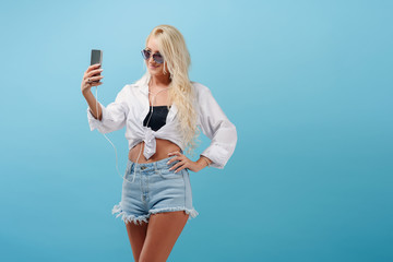 Young slender blonde girl with long hair, in summer clothes is holding a smartphone and making selfie. Dynamic music plays in the headphones. The model stands on a blue isolated background