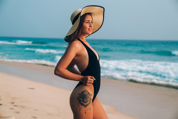 Side view of a young pretty girl in a black swimsuit, has a sexy tattoo on her thigh, wears a fashionable hat, looks at the sun, walks along the beach.