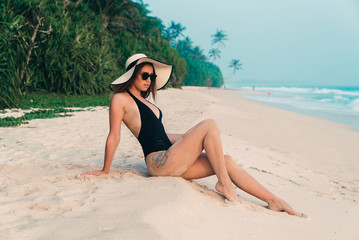 A slender young girl rests not on a white empty beach with palm trees and tropical jungle, dressed in a black swimsuit, hat, wearing stylish black sunglasses.