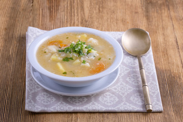 Fresh vegetable soup made of carrot, potato, cauliflower, parsley and rice in white plate,
