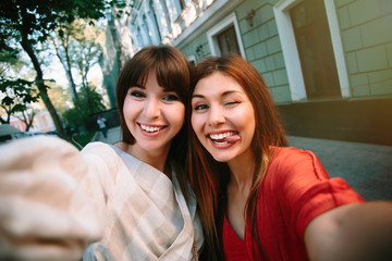 Close up lifestyle portrait of girls best friends makes funny faces on mobile  camera , show tongue and laughing together.Two young  women posing outdoor, warm summer evening.