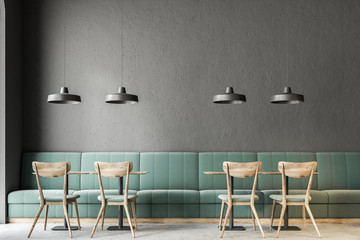 Dark gray wall bar interior, green sofas